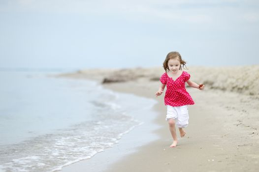 Adorable little girl on a sandy beach
