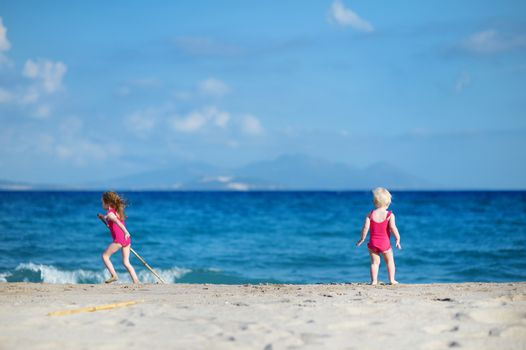 Two sisters playing on a sandy beach