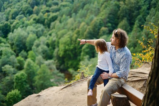 A girl and her father sitting on the edge