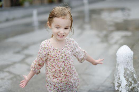 Adorable little girl having fun by a fountain