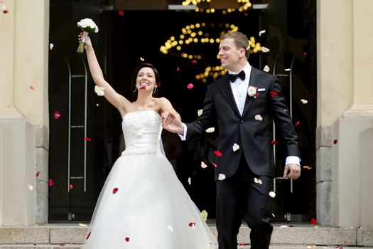 Just married couple under a rain of petals