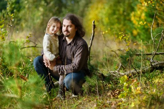 Young father and his little daughter at fall