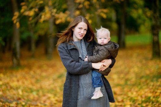 Young mother and her toddler daughter at fall
