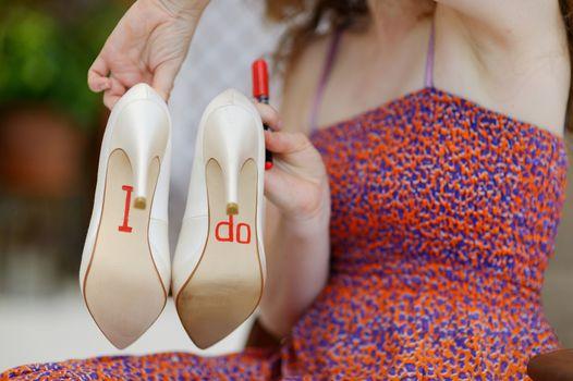 Bridesmaid displaying bride's shoes