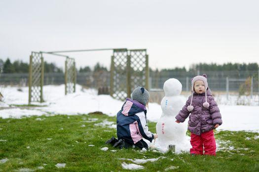 Little girls painting a snowman