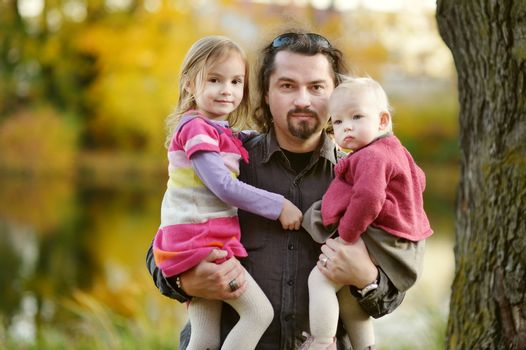 Young father and his daughters at fall