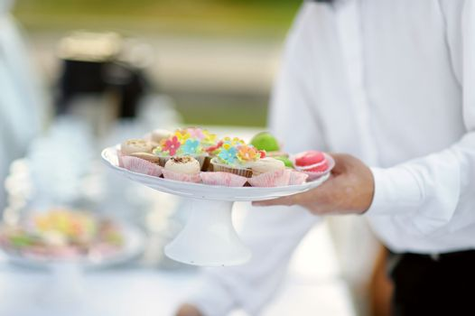 Waiter with dish of cupcakes