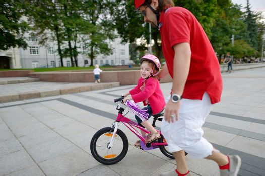 Young father teaching his daughter to ride a bike