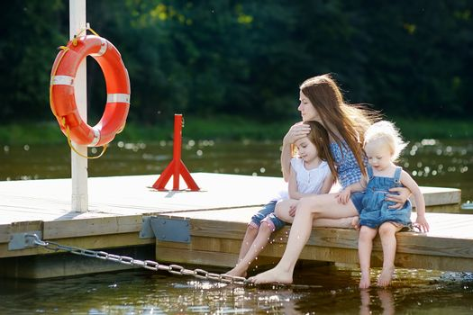 Mother and her children sitting on a wooden pier
