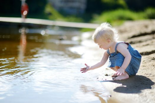 Adorable girl having fun by a river