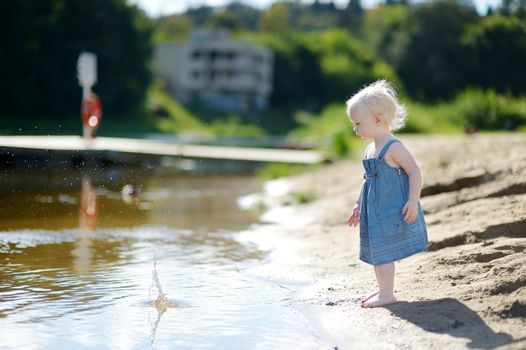 Adorable girl throwing stones into river