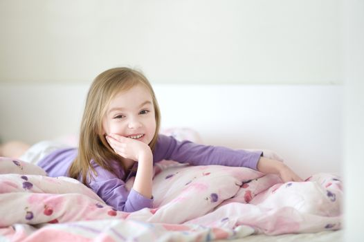 Little girl in pajamas on sunny morning