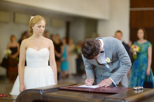 Groom signing a wedding contract
