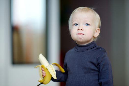 Toddler girl eating a banana