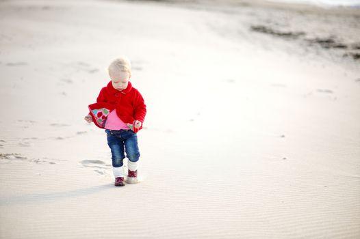 Adorable little girl walking by the seashore