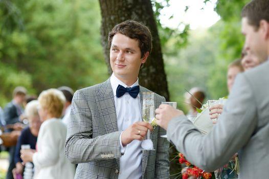 Wedding guests toasting happy groom
