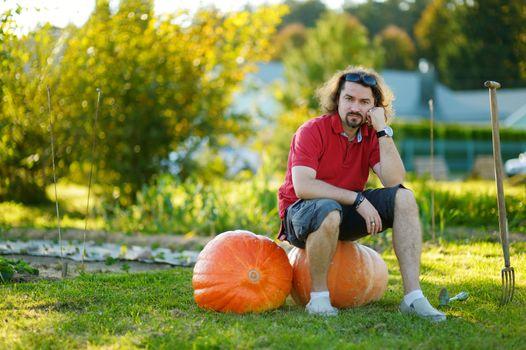 Young man sitting on huge pumpkins