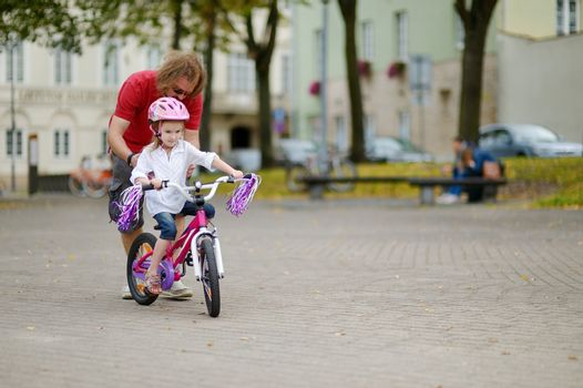 A father teaching his daughter to ride a bicycle
