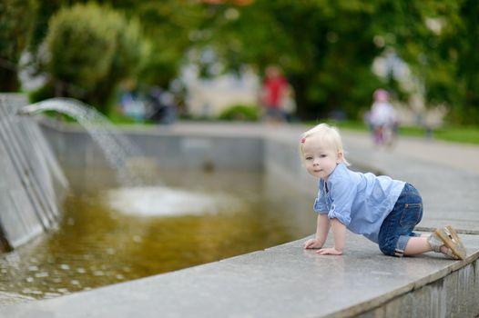 Toddler girl having fun by a city fountain