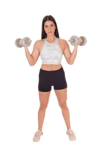 A beautiful young woman standing in shorts and sports bra from the front lifting her two dumbbells, isolated for white background