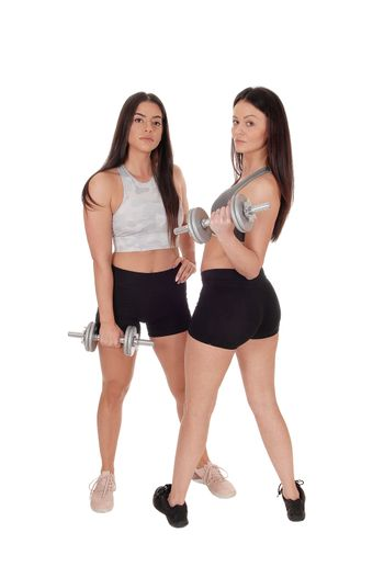 Two beautiful young woman standing in workout outfits in the studio working out with there dumbbells, isolated for white background
