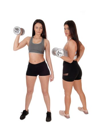 Two young beautiful woman standing in workout outfits in the studio working out with there dumbbells, isolated for white background