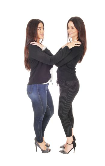 Two beautiful young woman standing face to face in jeans and heels looking at each other, isolated for white background