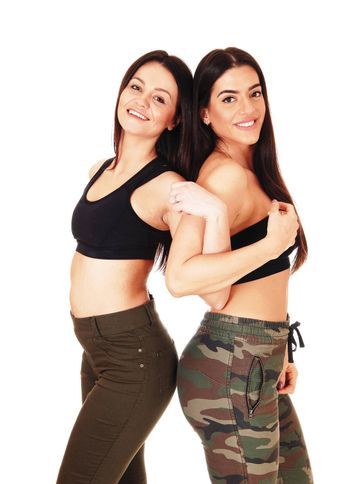 Two beautiful young woman standing back to back in jeans, smiling and looking at the camera, isolated for white background