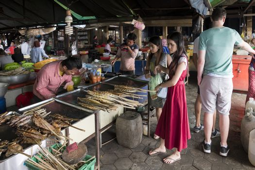 Krong Kaeb, Kep Province, Cambodia, 30 March 2018. Girls buying seafood skewers at the Crab Market