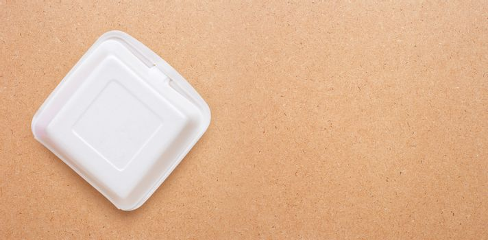 Foam food container on plywood background.  Copy space