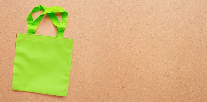 Green bag  on plywood background.  Copy space