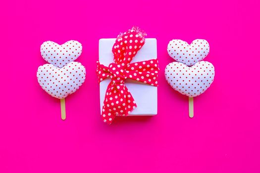 Gift box with Valentine's hearts on pink background. Top view