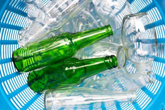 Glass bottles in blue waste basket.