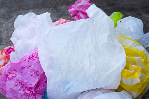 Colorful plastic bags on cement floor background