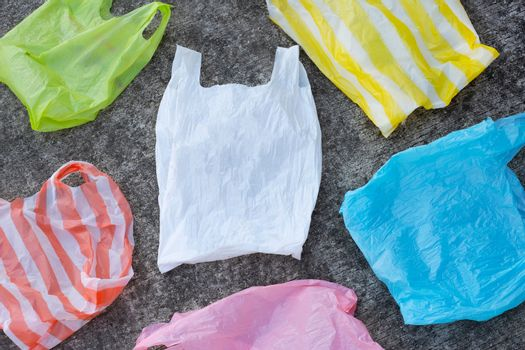 Colorful plastic bags on cement floor background.
