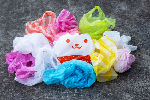 Colorful plastic bags on dark cement floor background