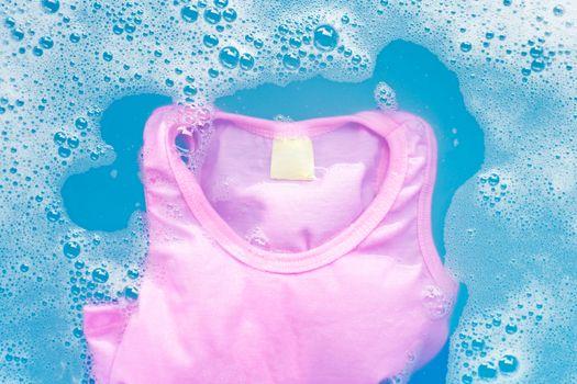 Pink kid sleeveless shirt soak in baby laundry detergent water d