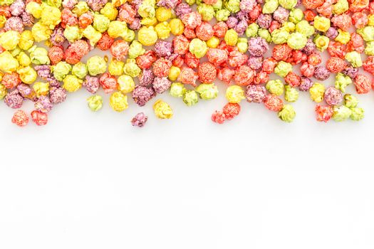 Flavored popcorn on white desk from above copy space