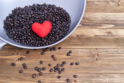 Close up red heart on pile coffee bean in pan
