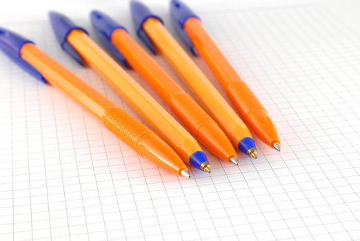 Five pen on the checked paper of notepad. Shallow DOF