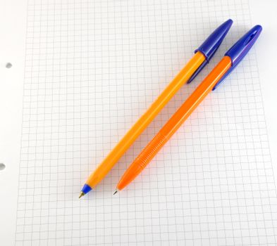 Two pen on the checked paper of notepad