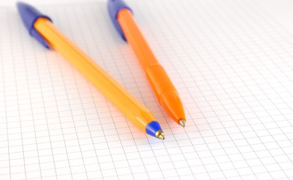 Two pen on the checked paper of notepad. Shallow DOF