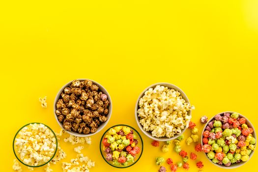 Flavored popcorn on yellow table from above space for text