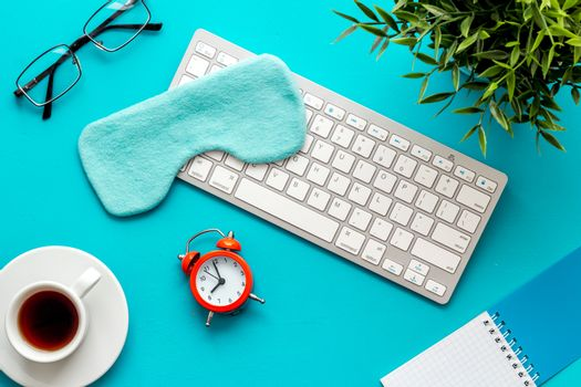 fatigue concept. Sleep mask on blue office desk from above