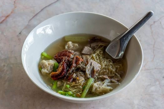 Roast duck wonton chinese egg noodle soup with vegetable in bowl