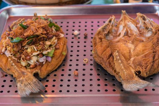 Fried fish with turmeric and garlic is a food in Thai street food market at Bangkok Thailand