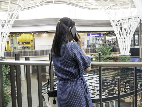 Asian young woman standing and talking by phone at the mall in Chiang Mai.