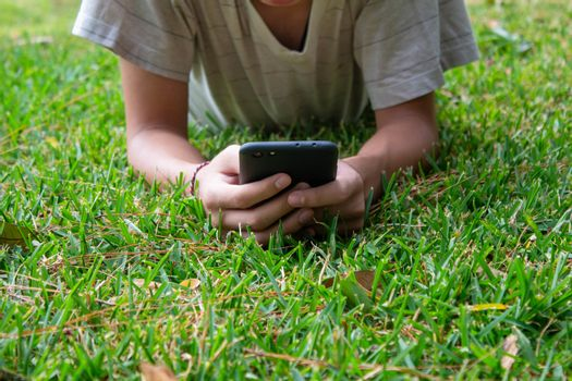 Asian teen boy lying on grasses ground in the garden and using smartphone happily.