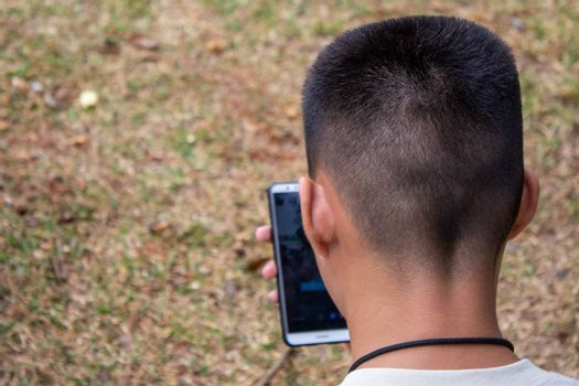 Asian teen boy sitting on grasses ground in the garden and using smartphone happily.