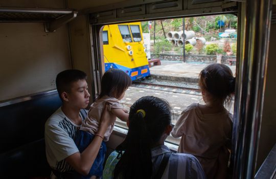 Asian family sitting on the train and looking to outside through the window.